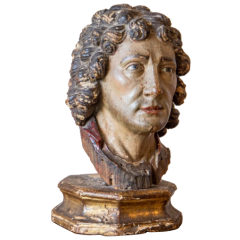 A carved polychrome wooden bust of a man