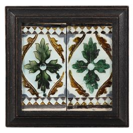 A mid 16th century pair of blue and brown glazed Spanish ceiling tiles with leaf motif