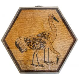 A small hexagonal folding table with a bead-work image of storks
