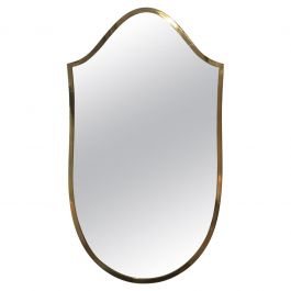 A small Italian 1950s brass shield shaped mirror