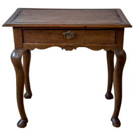 A George III oak lowboy with quirky legs