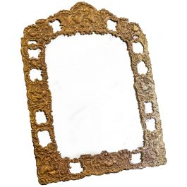 AN UNUSUAL REPOUSSE GILT BRASS EASEL MIRROR