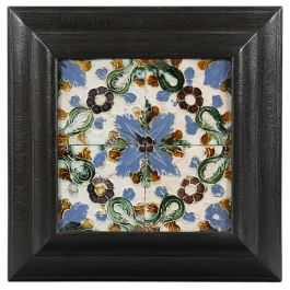 A mid 16th century set of four of blue and brown glazed Spanish tiles